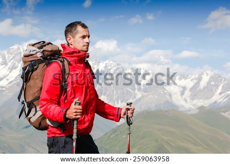 Successful man mountain hiker with backpack on the top of mountains - stock photo