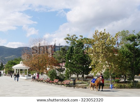 SUDAK, RUSSIA  - SEPTEMBER 24, 2014: Autumn view of embankment of township with walking people