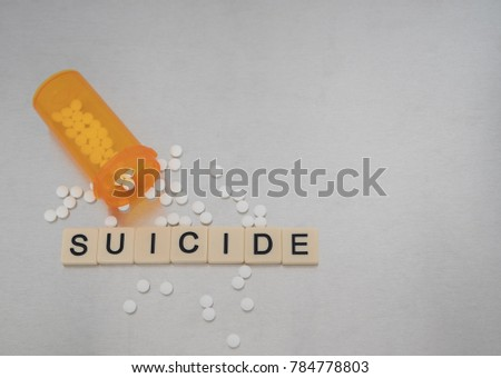 """Suicide"" spelled with tile letters placed in a row with an open bottle of oxycodone tablets. Photographed from above on a stainless steel background. Image has copy space."