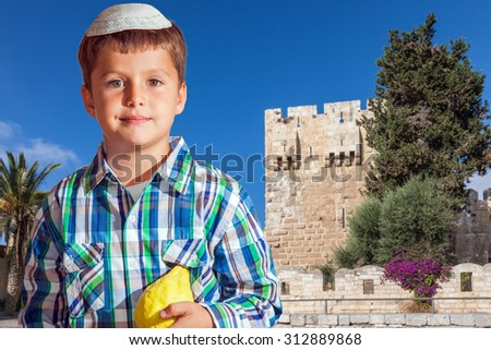 Sukkot in Jerusalem. Charming seven year old boy in white festive skullcap with etrog - stock photo