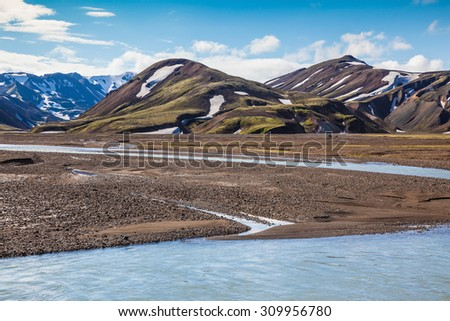 Summer flood of meltwater blocks the way to tourist camping. The picturesque valley in national park Landmannalaugar, Iceland - stock photo