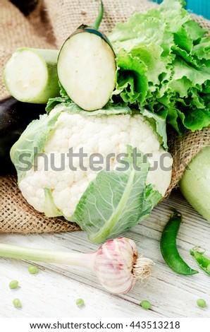 Summer fresh ripe vegetables,blue eggplant , green zucchini , peas, cauliflower, lettuce and garlic on a wooden background  - stock photo