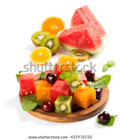 Summer fruit salad (watermelon, kiwi, orange, cherry, mint) with ingredients leaves on a  wooden plate isolated on a white background. - stock photo