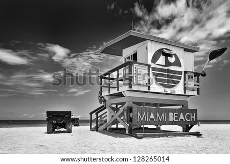 Summer scene in black and white with a typical lifeguard house in Miami Beach, Florida with cloudy sky and ocean in the background - stock photo