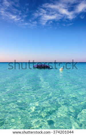 SUMMERTIME. The most beautiful sandy beaches of Apulia: inflatable mattress anchored white buoy. Porto Cesareo beach.-ITALY (Salento)-  - stock photo