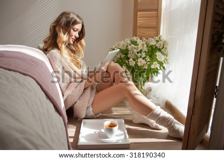 sun is shining into the bedroom,she looks out the window.lady sitting next to the bed,woman in the morning to read electronic books.Woman reading, the sun was shining into the room - stock photo