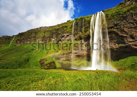 Sunny day in July. Seljalandsfoss waterfall in Iceland. Large rainbow decorates a drop of water - stock photo