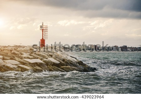 Sunset at the harbor with waves against old lighthouse on rocks - nature and Holiday concept - stock photo