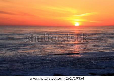 Sunset on the Gulf of water covered by ice