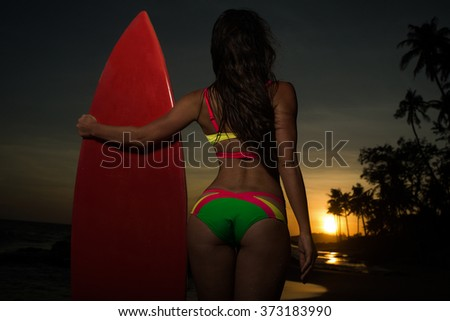 Surfer girl in bikini with red surfboard on a beach at sunset or sunrise