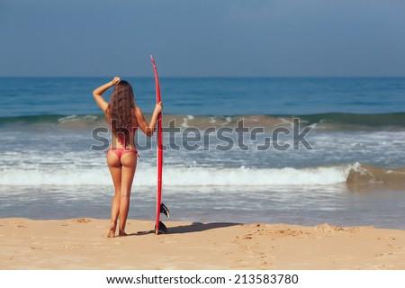 surfer girl in bikini with white surfboard on a beach - stock photo