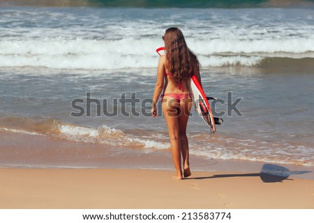 surfer girl in bikini with white surfboard on a beach go to the - stock photo