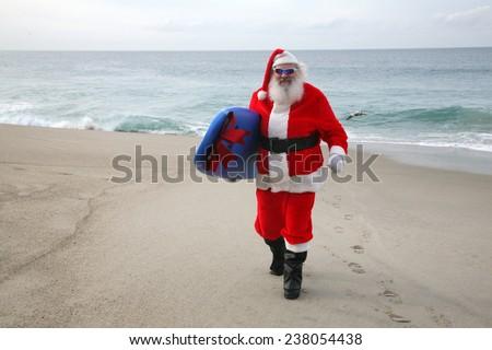 Surfing Santa Claus, Saint Nicholas,  Father Christmas, Kris Kringle, Santa, Sinterklaas, Saint Nicholas,  Father Christmas,  ?axta Baba aka Froze Dad, Christkind aka Christ child,  P�¨re No�«l,  - stock photo