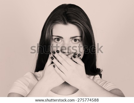 Surprised young woman covering mouth with hands and staring at camera emotion - stock photo
