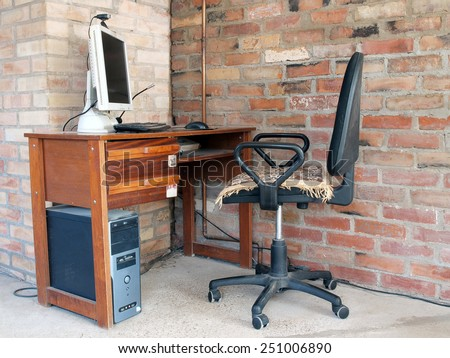 Table with desktop computer in room corner near red brick wall       - stock photo