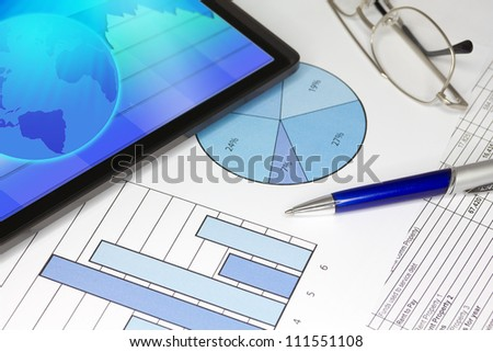 Tablet Computer in ipade style with Blue Pen Spectacles Figures and Graphs - stock photo