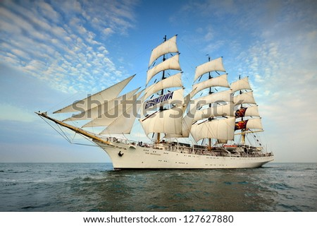 Tall Ship under sail with the shore in the background - stock photo