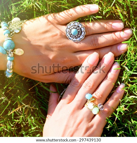 Tanned Female hands with summer bright retro bracelet and rings on green grass. Accessories with turquoise stone. Multicolour ring. Summer fashion concept. Adorable tenderly bijouterie.