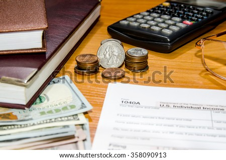 1040 Tax form for 2016 with pen, glasses, dollars and calculator