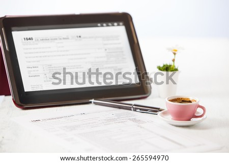 1040 tax form on tablet - stock photo