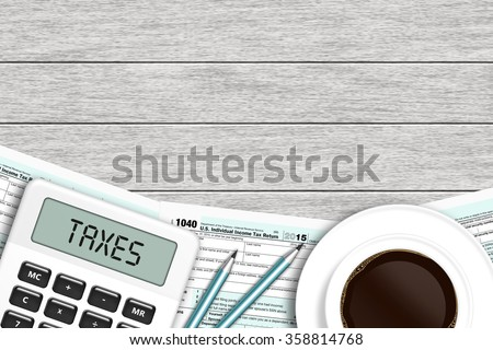 1040 tax form with calculator and coffee lying on wooden desk with place for text - stock photo