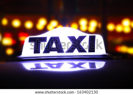 taxi sign illuminated at night - stock photo
