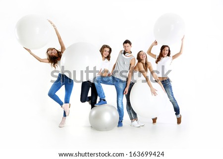 Team of five young people dressed in white shirt and jeans posing with giant balloons  / Group of happy young friends - stock photo