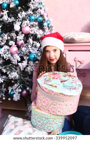 teen girl in santa hats seat under christmas tree with presents
