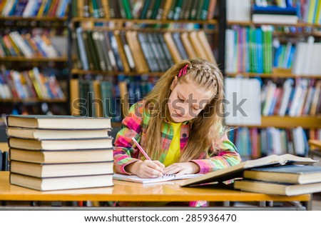 teen girl studying in the library - stock photo