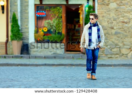 teenage boy crossing the street of old town - stock photo