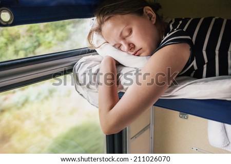 Teenage girl sleeps in train on the top bunk. - stock photo