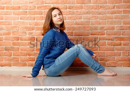 Teenager girl. Brick wall background.
