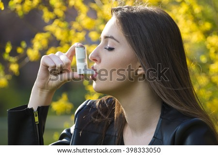 Teenager girl using asthma inhaler in park - stock photo