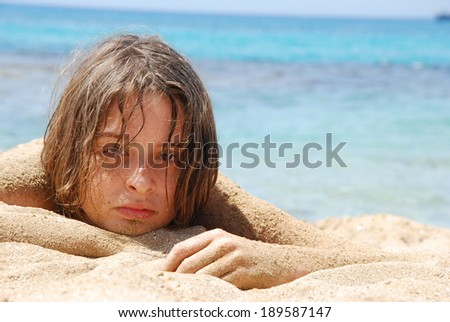 Teenager laying down on a beach, with the sea in the background.