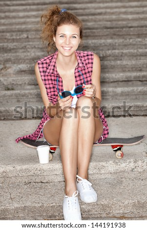 teenager with cup of coffee sitting on skateboard against stairs. Lifestyle - stock photo