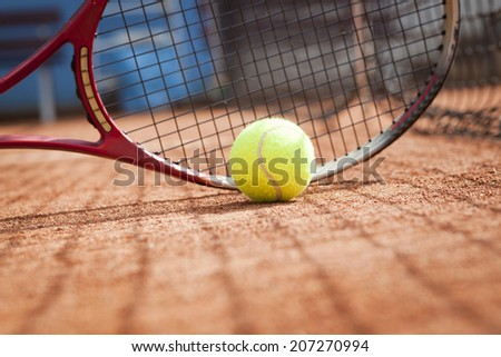 tennis racket and tennis ball on the clay court - stock photo