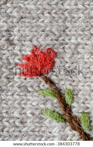 Texture of gray sweater with a red flower, handmade - stock photo