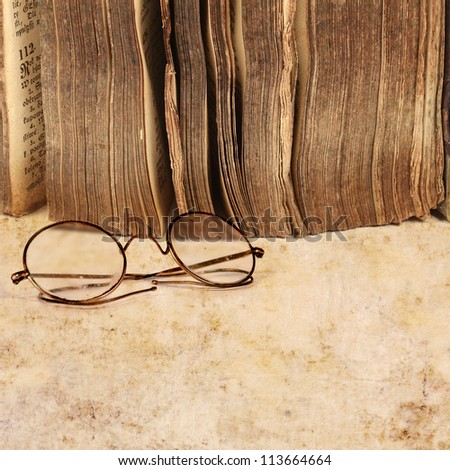 17th century book with vintage glasses, on grunge paper background - stock photo
