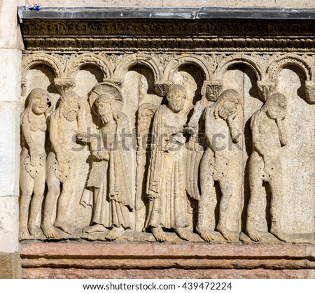 11th century carving of the Creation and Fall on the Modena's Cathedral facade. The figures are carved in high relief, giving them a strong sense of three-dimensionality. - stock photo