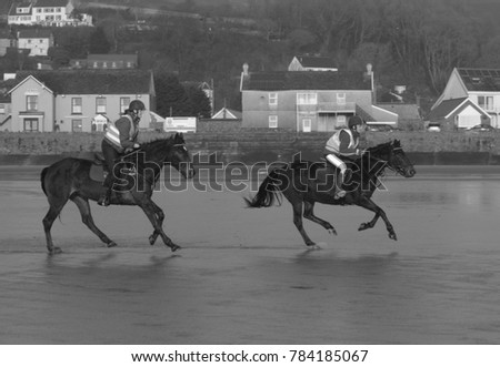 30th December 2017- Horse riders galloping on the sandy beach at Pendine, Carmarthenshire, Wales, UK.