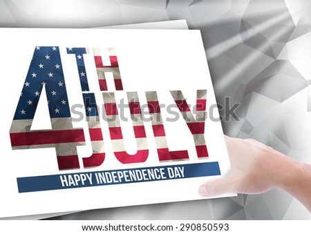 4th july Happy Independence Day flag in text on paper and hand holding