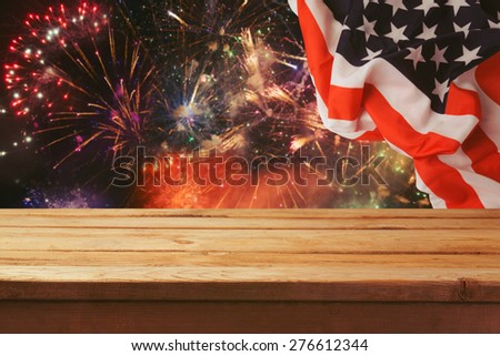 4th of July background. Wooden table over fireworks and USA flag. Independence day celebration - stock photo