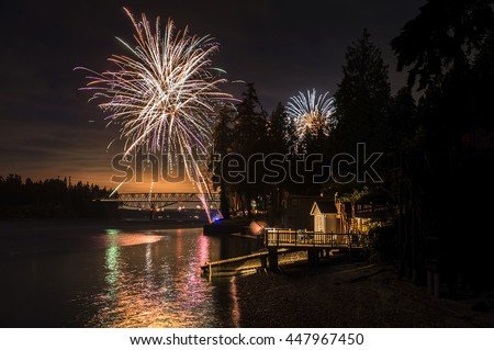 4th of July Fireworks Display. Independence Day signals fireworks and beach BBQ. Here the celebrations take place at Agate Pass between Bainbridge Island and the Olympic Peninsula, Washington state. - stock photo