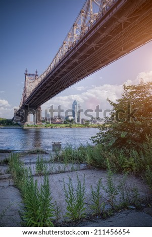 57th street bridge in NYC with cloudy blue sky with sunshine - stock photo