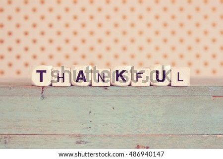 """THANKFUL"" printed on dice against rustic wood background and polka dots"