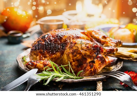 Thanksgiving day dinner table setting with whole roasted turkey or chicken on plate with cutlery , festive lighting and decoration, close up