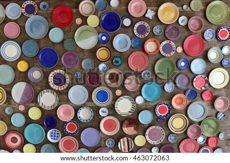 The art colorful plates placed on the cement floor for background.