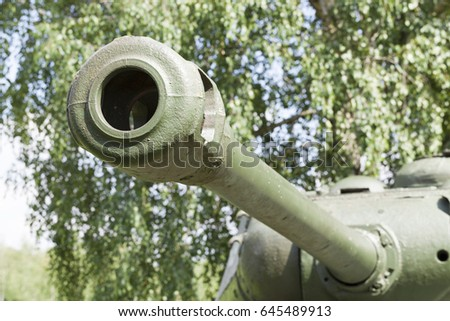 the barrel of the old Soviet gun, tank, located in the park. Photo close-up, small depth of field. Summer season