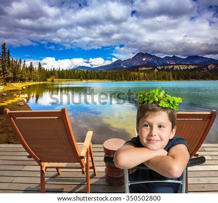 The beautiful boy in carnival wreath. Two convenient chaise lounges on the bank of round lake - stock photo