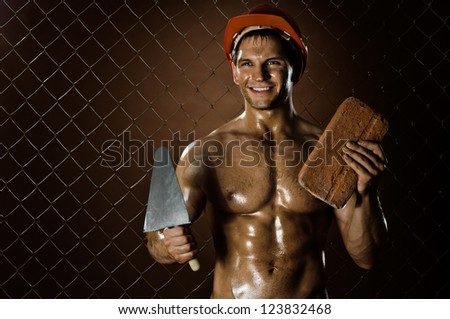 the beautiful  muscular worker  man, in  safety helmet  with trowel and brick  in hands and smile, on netting fence background - stock photo